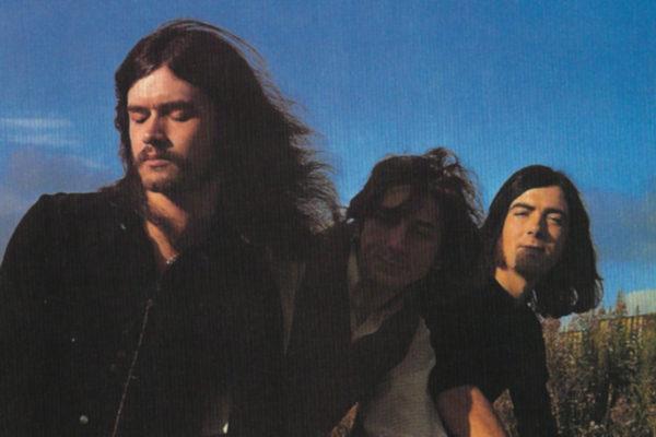 Glenn Hughes (chant, basse électrique), Dave Holland (batterie) et Mel Galley (chant, guitare électrique)